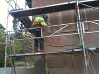 En av våra blästrare använder våtbläster effektivt vid fasadblästring